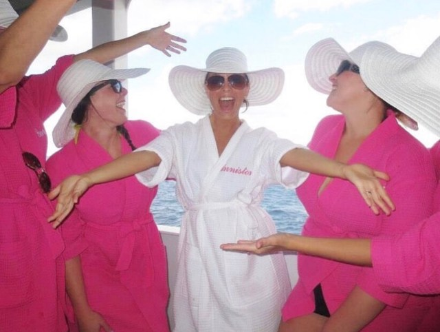 five girls on a cruise boat balcony wearing matching robes and hats
