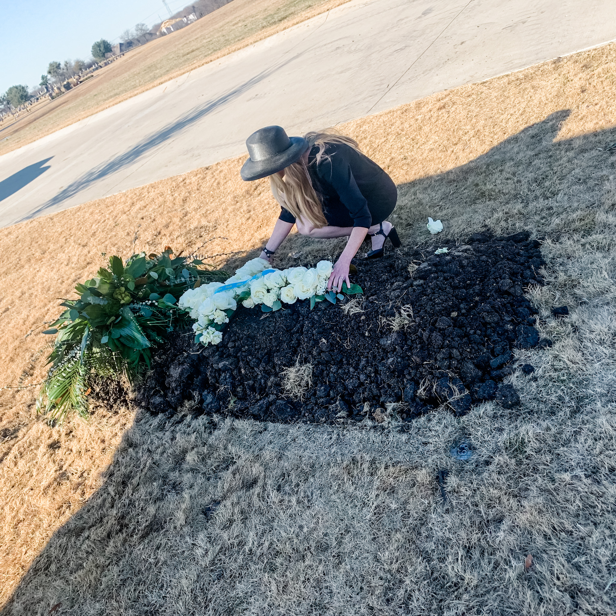 Grieving crying woman at grave of father who died from Covid 2020