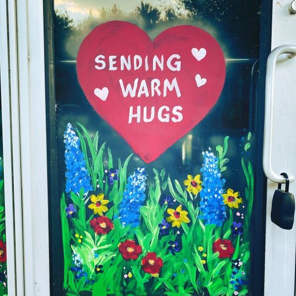 """Pet store door that says """"Sending warm hugs."""""""