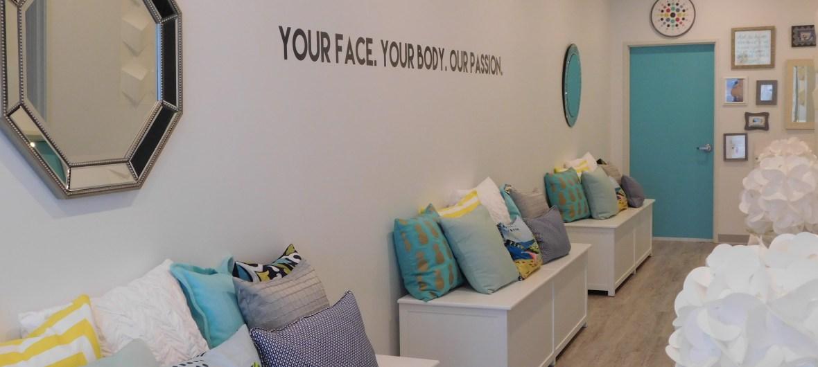 """Benches with pillows inside Heather Brown Face and Body Studio. Wall reads """"Your Face. Your Body. Our Passion."""""""