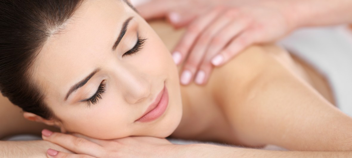 Young woman gets massage while relaxed with eyes closed