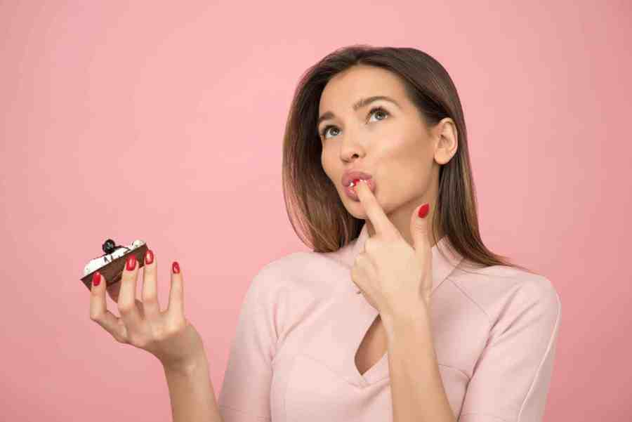 Woman tasting cake frosting with her finger.