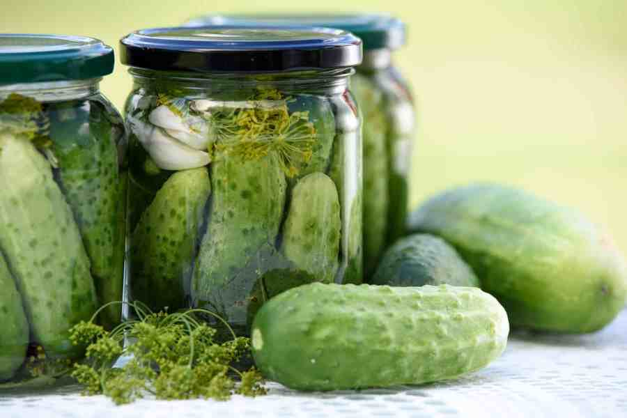 Fermented Foods: Two jars of pickles with loose pickles laying on table.