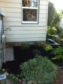 Side of front porch with rock area for drainage and new bushes.