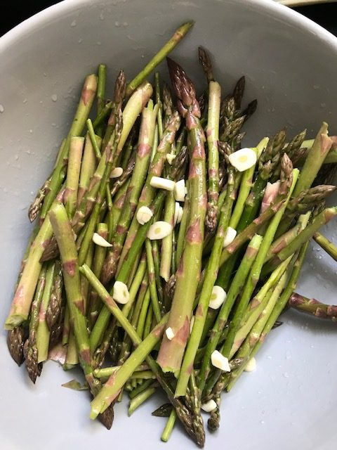 mixing the ingredients for baked asparagus #heatherearles #herbnwisdom #naturalliving #asparagus #dinnerrecipes #author #podcaster #gardenfood