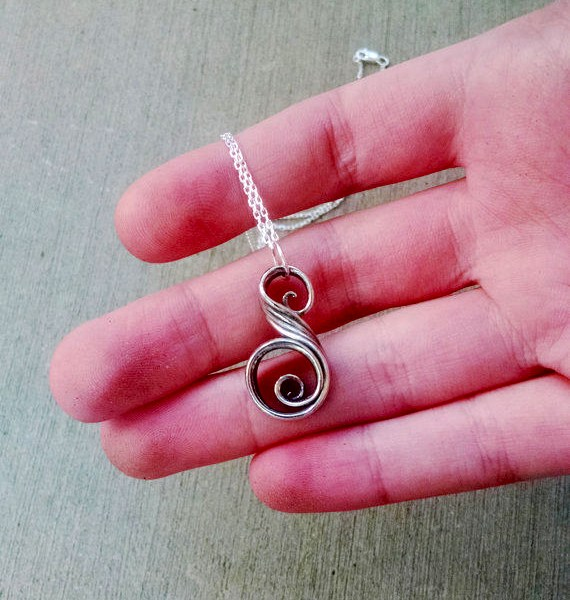 swirl necklace in a hand