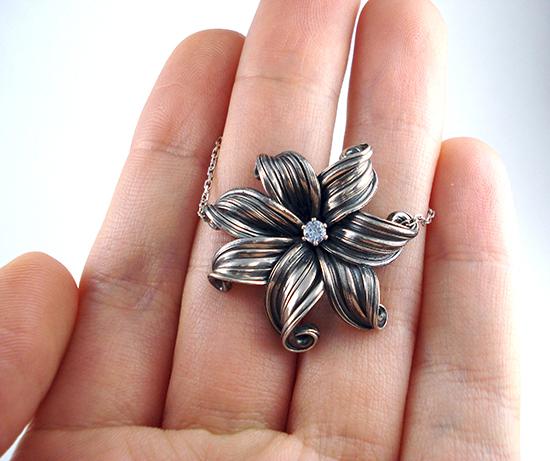 mitsuro flower necklace in hand