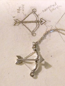 Finished bow and arrow necklace next to sketch