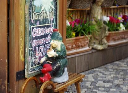 Un nain devant un restaurant de Prague.
