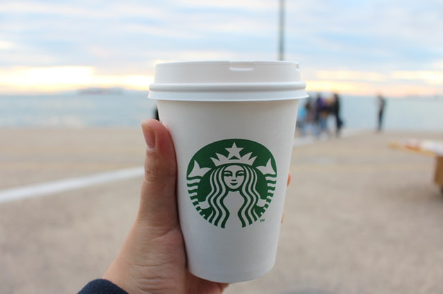 a person holding a coffee cup with starbucks logo