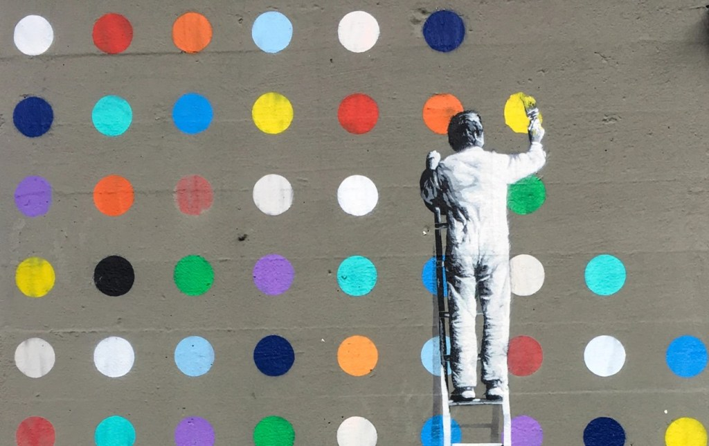 ppi vs. dpi image of man painted on a wall painting dots on the same wall