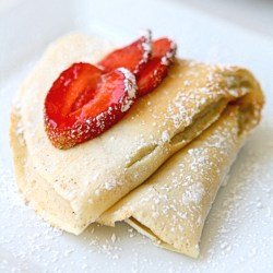 Folded crepe with sliced strawberries on a white plate