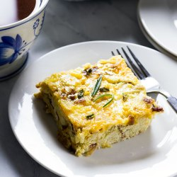 Slice of egg, potato and cheese casserole garnished with rosemary leaves on a white plate, with a fork and a blue and white mug of coffee