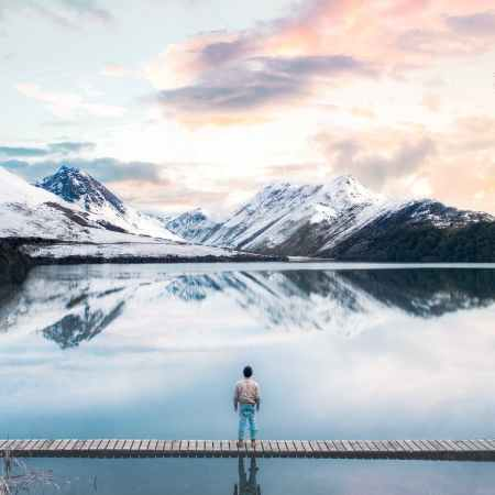 back view of a person standing on wooden planks across the snow capped mountains
