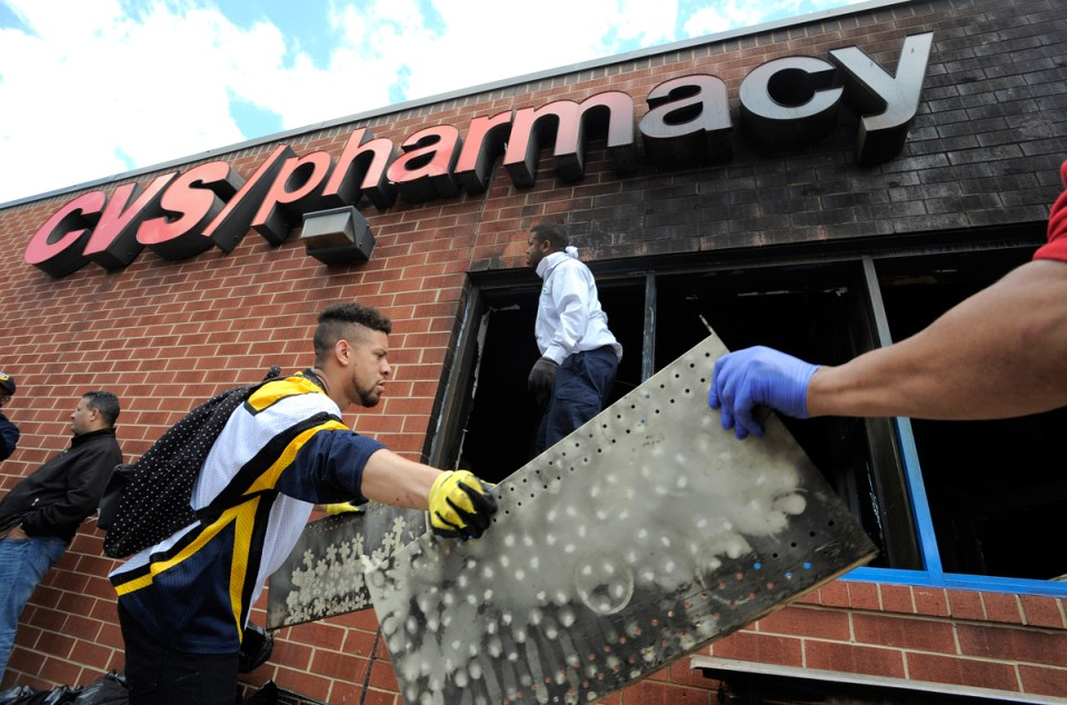 Volunteers work to help clear out the debris from a CVS in Baltimore, Tuesday, April 28, 2015. Maryland's governor vowed there would be no repeat of the looting, arson and vandalism that erupted Monday in some of the city's poorest neighborhoods.