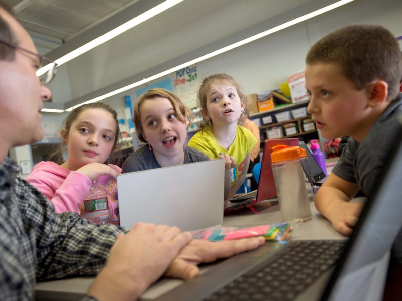 Greenbush elementary school fourth-grade teacher Chris Allen, left, works with, from left, Alexa Stroker, Elissa Dorgan and Connor Moreau on a math problem.