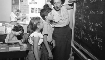 Young students get help in reading problems at a summer reading clinic run by the New York City Board of Education, July 28, 1955. The teacher helps two pupils to recognize words through phonics.