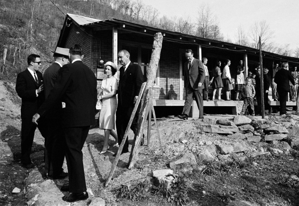 President Lyndon Johnson and his wife, Lady Bird, center left, leave the home in Inez, Ky., of Tom Fletcher, a father of eight who told Johnson he'd been out of work for nearly two years, in this April 24, 1964, file photo. The president visited the Appalachian area in Eastern Kentucky to see conditions firsthand and announce his War on Poverty from the Fletcher porch.
