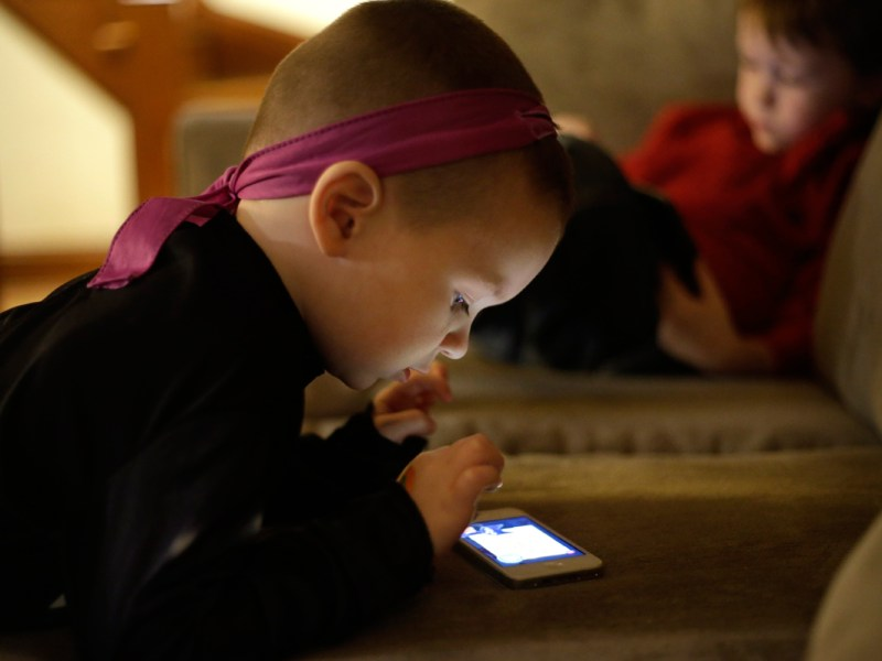 Nolan Young, 3, front, looks at a smart phone while his brother Jameson, right, 4, looks at a smart tablet at their home, in Boston.