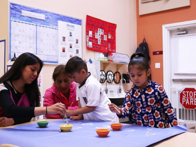 Maria Lemus, far left, paints the alphabet with siblings Adrian and Kimberly Lorencillo and their grandmother before most of the other students arrive.