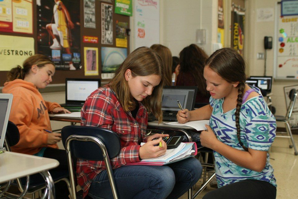In this photo taken Tuesday, Oct. 9, 2015, eighth graders Hannah Therauilt, left, and Taylor Tantaquidgeon work together on algebra problems in Mark Olsen's classroom at Thomaston High School in Thomaston, Conn.