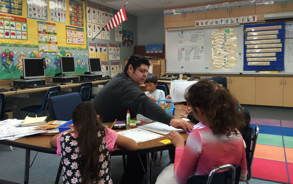 Octavio Gutierrez works with a group of students learning English, giving them a preview of what their fluent peers will learn later.
