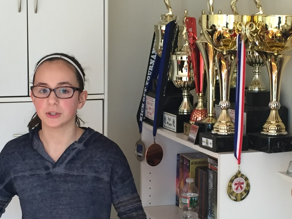 VLACS middle school student Olivia Rando, 11, stands beside some of the trophies she's won as a black belt in karate.