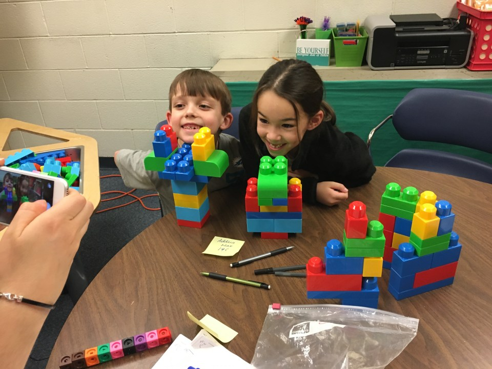 Two Forest Grove Elementary School students show off their block structures for Nesra Yannier to photograph during an experiment.