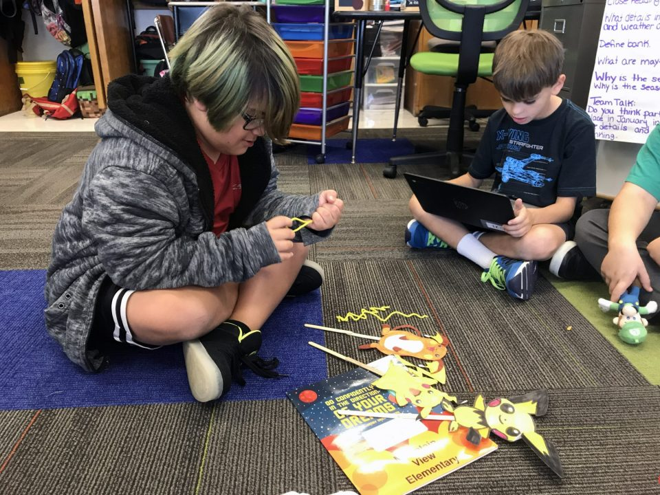 A fourth-grader makes a puppet while his teammate works on writing a script at Mountain View Elementary School in Longmont, Colo.