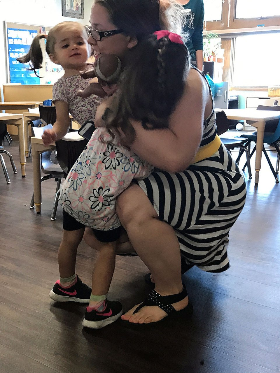 Sarah Sheikh, 2, foreground, greets her mother, Meghan, and younger sister with a running hug. Meghan says both daughters are now happy to spend the day in a child care program at the Center for Child Development at Wichita State University in Kansas.