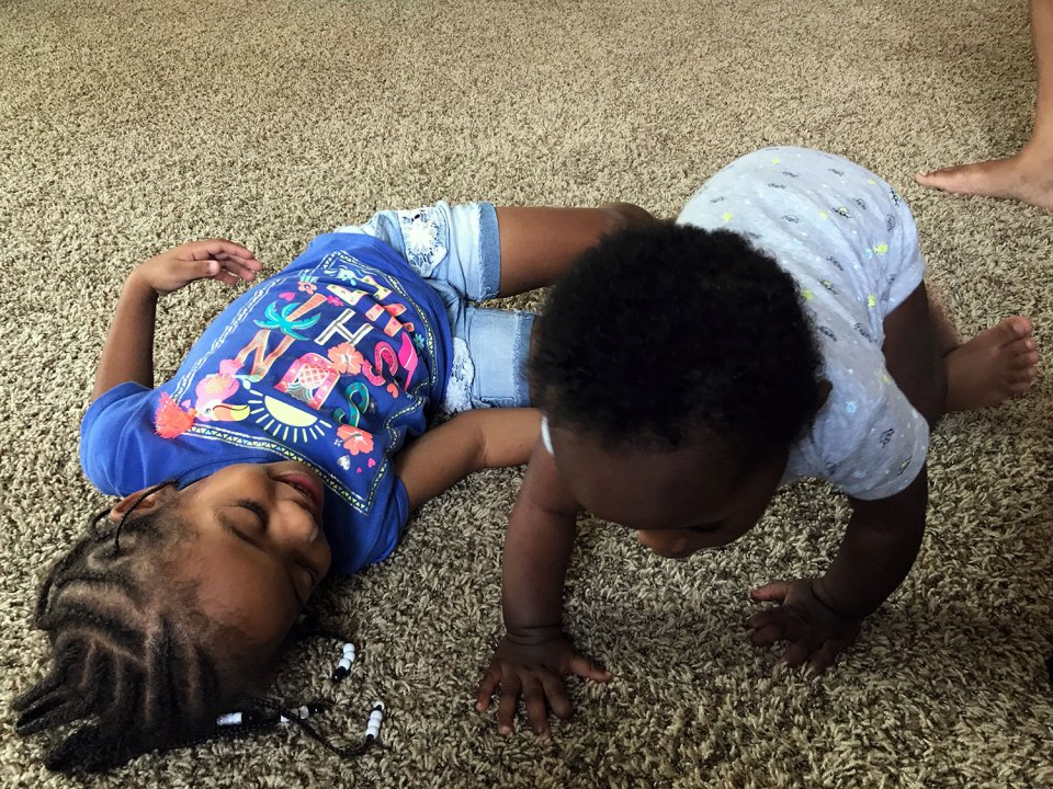 I'mari Hudson, 3, plays with a younger child at Kanetha Brown's home-base child care facility in Wichita, Kan. Reed's mother likes that her daughter is always busy playing or singing or listening to books during the day.