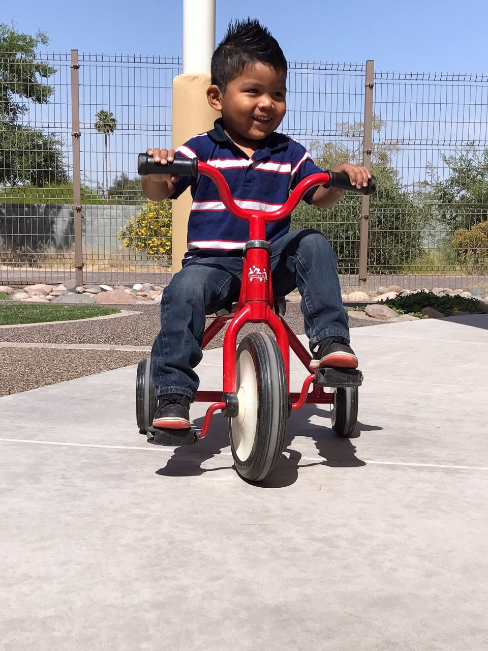 Nathan Jaramillo rides a tricycle during outdoor time at Educare Arizona in Phoenix. Improved gross motor skills are an important part of healthy development for 2-year-olds. Lillian Mongeau/The Hechinger Report