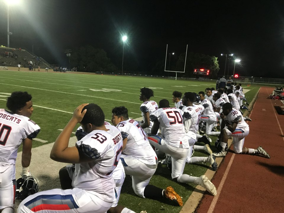 KIPP players kneel while medics help an injured KIPP player.