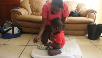 Nurse Polita Williams weighs 8-month-old Jamir during a home visit.