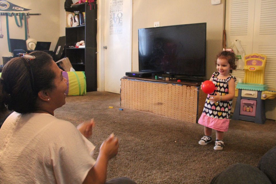Mercedes Castillo throws a ball to 2-year-old Sonja Morales during a home visit.