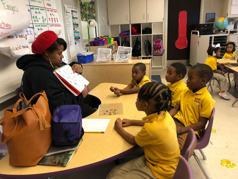 A kindergarten teacher works with a small group of students at KIPP Morial charter school in New Orleans, while other students work on personalized learning software.