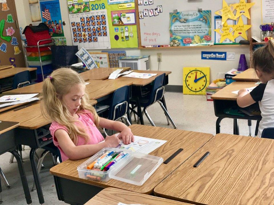 Pre-K student Caroline Larsen, 5, focuses on a class worksheet at Zion Lutheran School in Seymour, Indiana.
