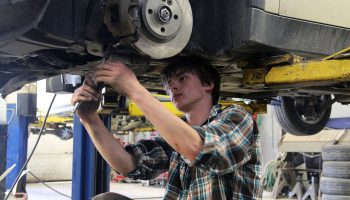 A high school student repairs a car in an automotive shop class. Jobs in automotive body repair are relatively safe from automation, and they don't require a college degree.