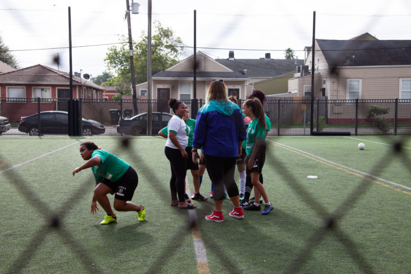 """Girls Coach Katie Lucky-Heard (left, white shirt) delivered a half-time pep talk to her team. """"Tú puedes,"""" she said. You can do it."""