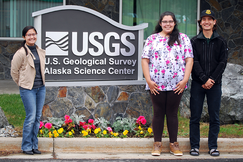 "Parker Pickett, 18, stands with Evangeline Dooc (left) and Lauryn Yates (center), both 18, his fellow U.S. Geological Service interns outside the agency's Anchorage office. In a departure from their parents' career paths, all three ANSEP students plan to pursue careers in the natural sciences. ""The opportunities I have been given are things (my parents) weren't able to have,"" Yates said."