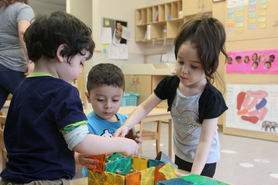 Students build a tower with blocks during center time in a Christopher House early childhood classroom.