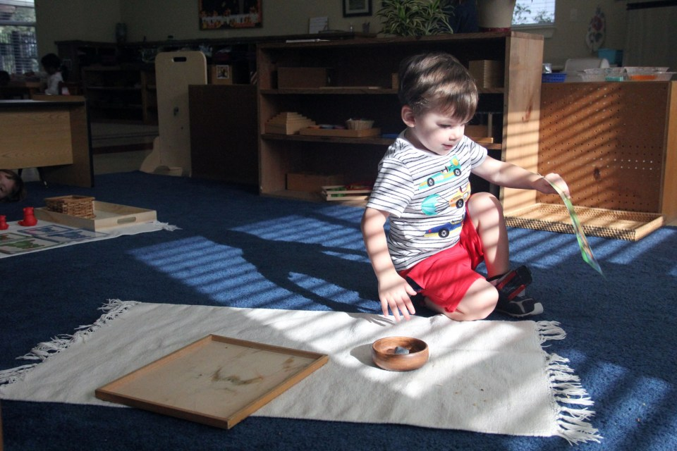 A child in a classroom for the youngest students at Hill Country Montessori sets up his workspace.