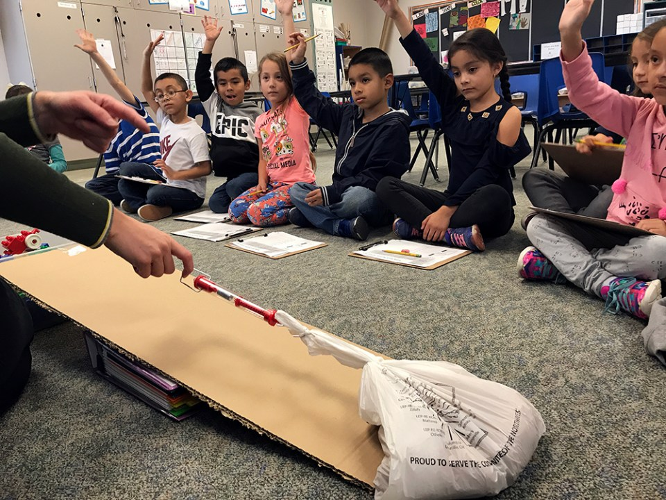 First-grade students at Pioneer Elementary School in Quincy, Washington, eager to try out the ramp their teacher is demonstrating during their STEAM enrichment class, raise their hands in hopes of getting a turn.