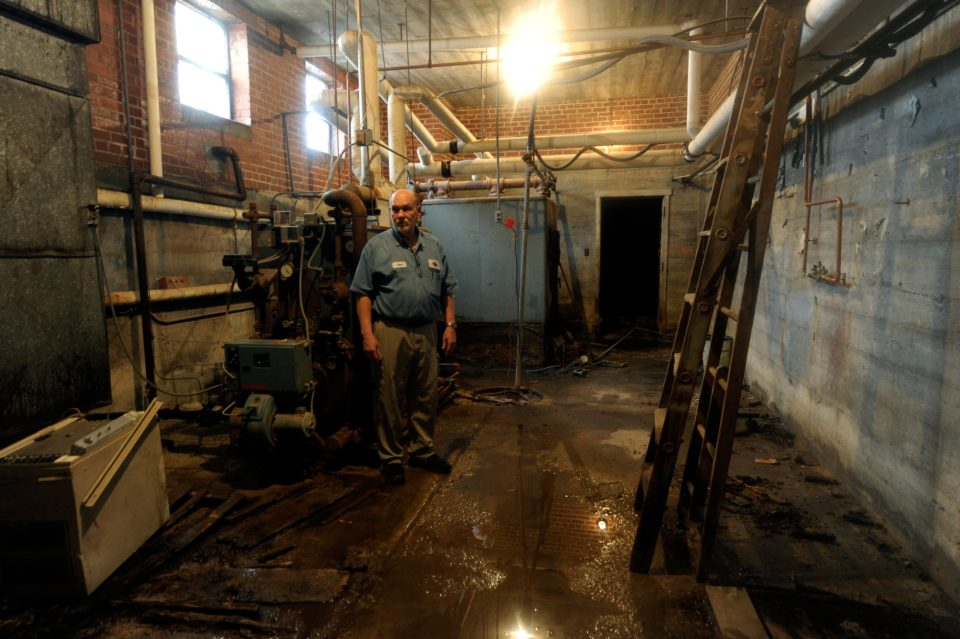 Dan Coder, custodian of Unified School District 377 for 35 years, looks over the broken boiler in the central office building which also houses the preschool and kindergarten classrooms.