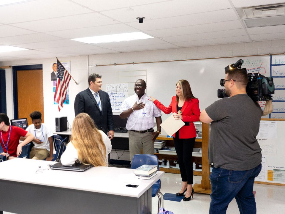 Tulsa Public Schools Superintendent Deborah Gist presents a Golden Apple Award to Dr. Abraham Kamara at Memorial Junior High School.