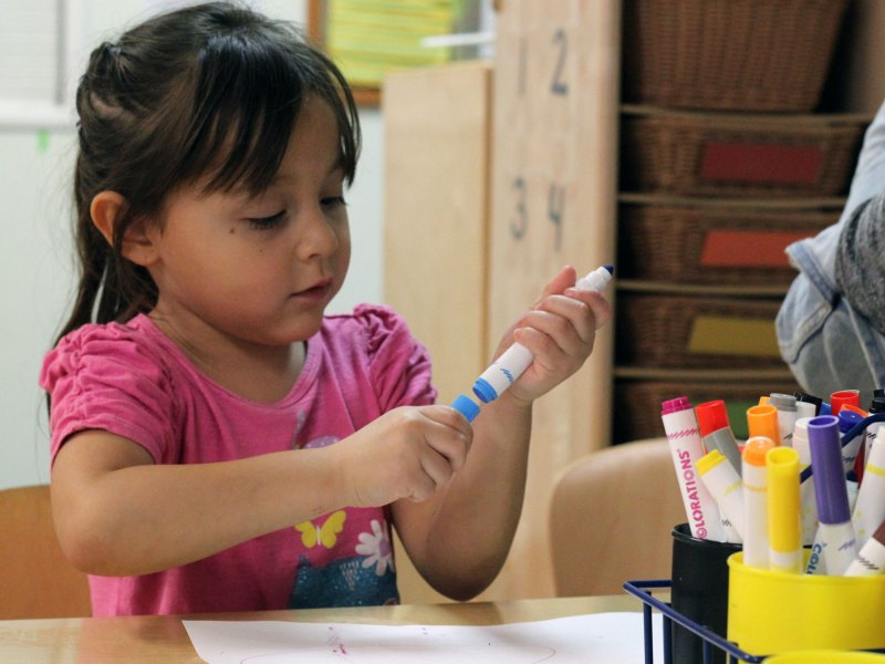 A student at a Kidango child care center in San Jose colors during play time.