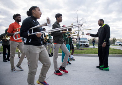 Band director Eric French, right, lifts the tip of a trombone as he watches Kirk Newman, Danielle Scott, and Kentrell Denson, from left to right, get in line. George Washington Carver School band in New Orleans gets ready for Mardi Gras in February 2019.