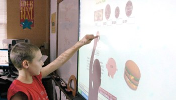 A student points to a coin and touches it as he works on a math project on the SMART Board, in his Southwest Elementary School classroom in Jefferson City, Mo. (AP Photo/The News Tribune, Julie Smith) No Reproduction
