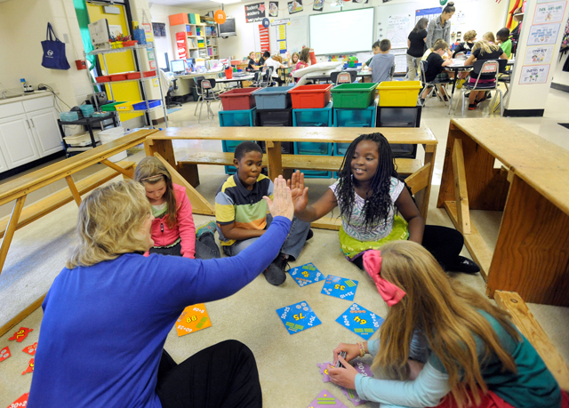 Third-grade teacher Sherry Frangia, left, high-fives student Jayla Hopkins during a math lesson at Silver Lake Elementary School in Middletown, Del. Tuesday, Oct. 1, 2013. Silver Lake has begun implementing the national Common Core State Standards for academics.