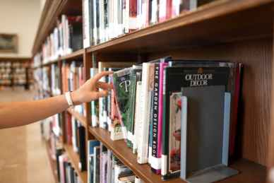 person holding book from shelf